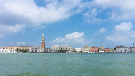 Horizontal photo with view on famous Venice cityscape with several landmarks. The photo is captured from a boat on the lagoon of Venice. Sky is clear with few clouds. Stock Photo - 129595688