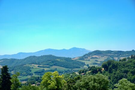Horizontal photo of rural country captured during summer time in Italy. View is from the edge of ancient Italian town Urbino. Several hills covered by trees are in front of clear sky.