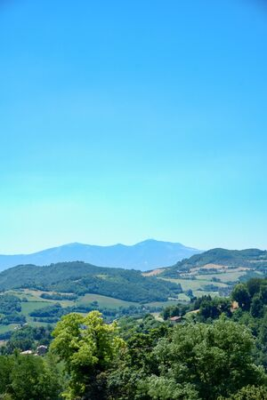 Vertical photo of rural country captured during summer time in Italy. View is from the edge of ancient Italian town Urbino. Several hills covered by trees are in front of clear sky. Stock Photo - 132368815