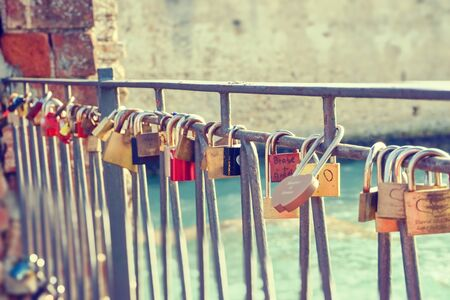 Horizontal photo of many color metal locks placed on the old fence. The locks have signatures and messages from lovers in the ancient town Sirmione in Italy next to castle. Stockfoto