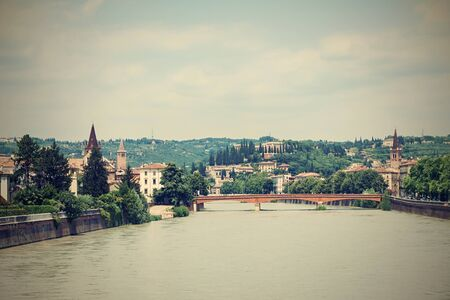 Horizontal photo with view on Adige river. River flows through famous Verona city in Italy. Old bridge and several buildings are visible in background. Sky is partially cloudy.