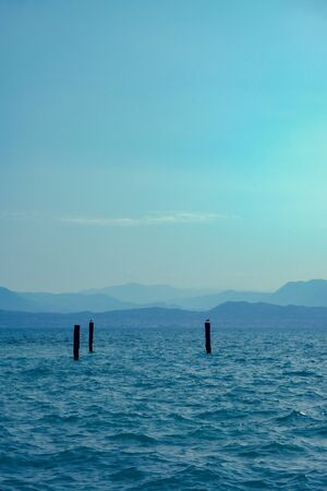Vertical photo with view over Lago di Garda. Lake in Italy has high mountains in background partially hidden in clouds. Few birds are perched on pillars.