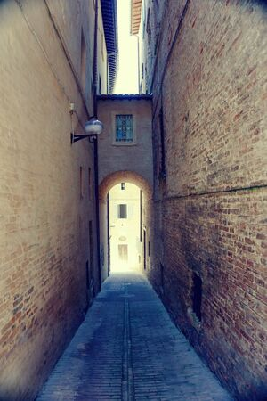 Vertical photo of very nice narrow street in famous Urbino town.  Buildings are on both sides with joining passage between them.