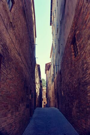 Vertical photo of very nice narrow street in famous Urbino town.  Buildings are on both sides built from ancient red bricks.