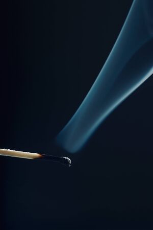 Vertical photo of match stick. The safety match has burnt black head but the body is still fine. Nice curly smoke goes from head to the space. Background is black. Stock Photo