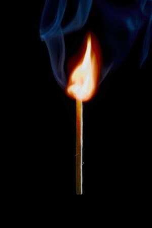 Vertical photo of match stick. The safety match has flaming hot head but the body is still fine. Nice curly smoke goes from head to the space. Background is black. Stock Photo - 136094764
