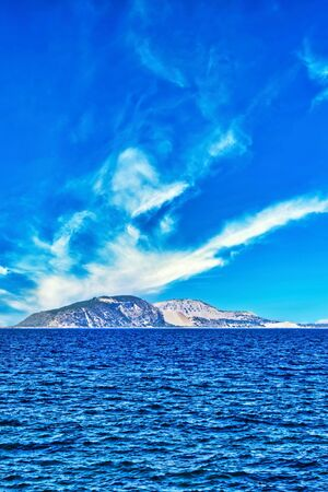 Vertical photo with view on small island in Aegean sea. Island is between Kos and Nisyros. Sky is blue with white clouds.