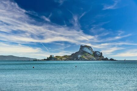 Horizontal photo with view on famous rock in Aegean sea with small chapel Agios Nicolaos. Rock is visible from Agios Stefanos Bay beach on Kos island. Stock Photo