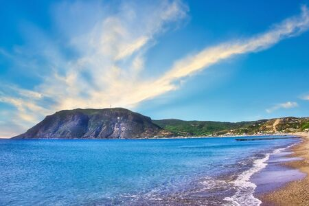 Horizontal photo with view on rock in Agios Stefanos Bay beach on famous Greek Kos island. Sky is blue with few clouds. Beach sandy with small stones. Stock Photo