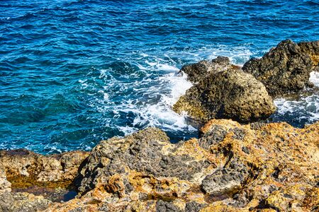 Horizontal photo with detail of rocks on sea shore near Nisyros island capital city. Sea is with waves and rocks are covered by orange color caused by sulfur. Stock Photo - 139416295