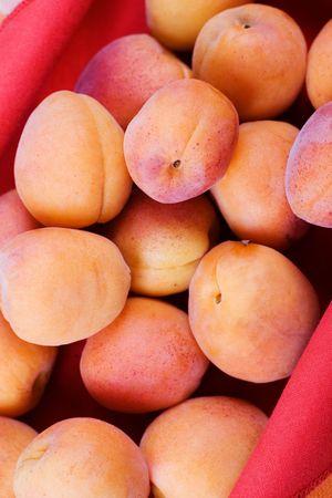 lien: Fresh apricots in red lien cloth upholstered basket.