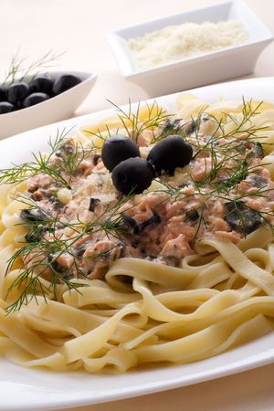 Pasta tagliatelle with salmon, black olives, dill and parmesan photo