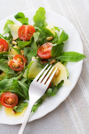 Ruccola salad with tomatoes, parmesan and pine nuts photo