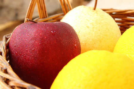 Variety of fruits into basket on old wood floor photo