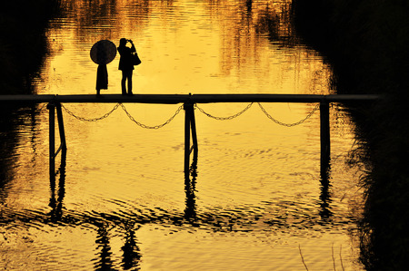 sightsee: Silhouette of two people during sunset