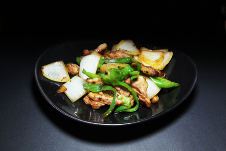 Green pepper fried pork in a plate on dark background