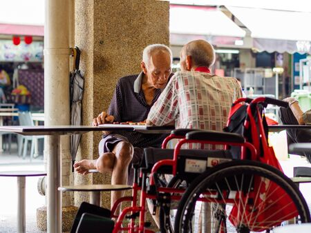 SINGAPORE, 12 APR 2019 - Two old male pensioners  retirees enjoy a game of Chinese chess in a hawker centre. Singapore has a rapidly aging population