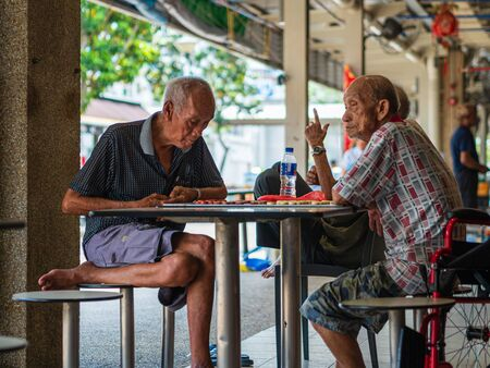 SINGAPORE, 12 APR 2019 - Old male pensioners  retirees enjoy a game of Chinese chess in a hawker centre. Singapore has a rapidly aging population Editorial