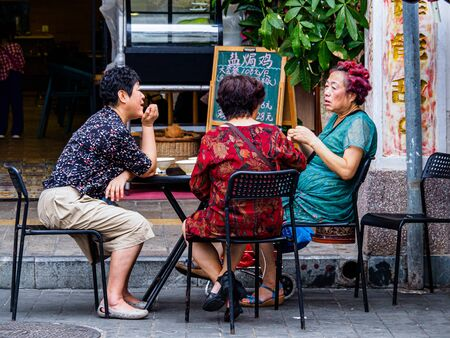 HAIKOU, HAINAN, CHINA – 2 MAR 2019 – Middle-aged Chinese women socialize outside a cafe. China has a rapidly aging population.
