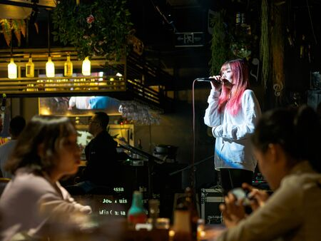 TIANJIN, CHINA - 5 OCT 2019 - A female singer performs at a live music bar in Tianjin China. Nightlife and entertainment theme