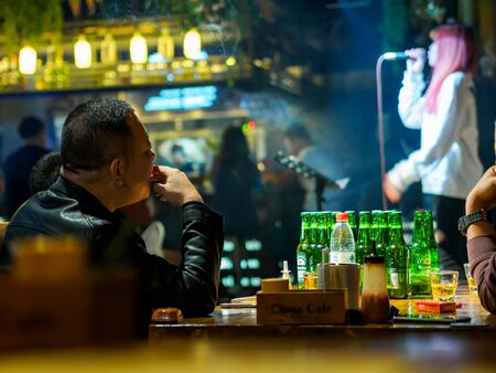 TIANJIN, CHINA - 5 OCT 2019 - A man drinks and smokes at a live music bar in Tianjin, China. Nightlife and entertainment theme Editorial