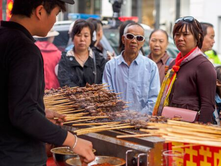 TIANJIN, CHINA - 6 OCT 2019 - Customers wait for their order of Xinjiang style grilled lamb skewers at a roadside food stall. Lamb skewers are a popular street food in China.