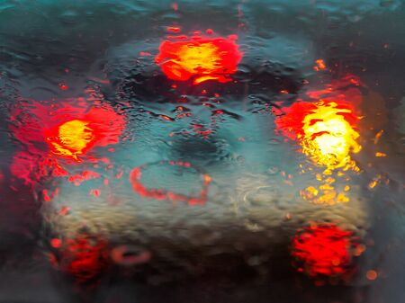 View of car traffic through a wet windshield - Traffic jam from a driver seat perspective on a rainy day. Tail-lights of the car in front reflected in the water droplets. To illustrate driving in the rain / road safety / wet weather driving