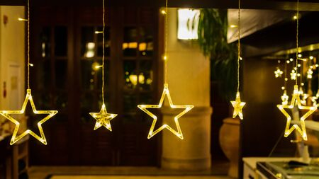 Warm yellow stars in a row against a diffused backdrop create a cosy  festive mood with copy space