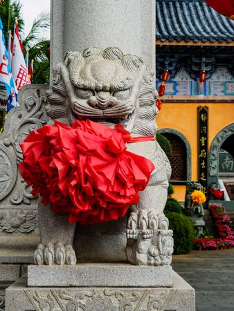 Chinese stone lion with festive red sash at the entrance of a Chinese temple in Hainan, China. Chinese text reads Dragon from calm clouds