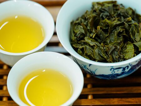 High angle close-up of two cups of green oolong tea and tea leaves on a wooden tray