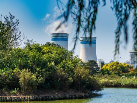 Cooling towers  smokestacks of a nuclear power plant spewing white smoke seen from within a scenic public park. To illustrate pollution and the dangers of nuclear power Stock Photo