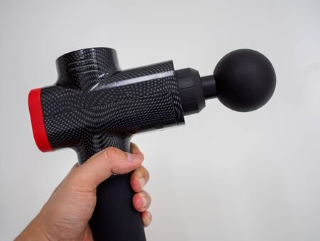 Hand holding a therapeutic percussive massage gun isolated against a white background with copy space Stok Fotoğraf