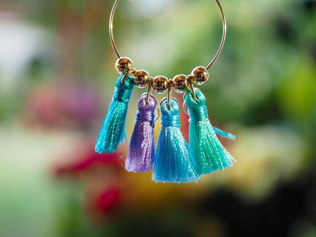 Close up of colourful home-made tassel earring against a blurred garden background - home-made craft jewellery concept. With copy space.