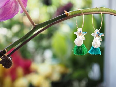 Close up of a pair of home-made earrings with pearls, crystal stars and tassels against a blurred garden background - home-made craft jewellery concept. With copy space