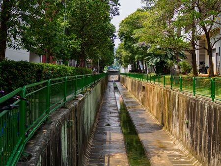 Tree lined water canal channel in a HDB residential housing estate in Singapore.