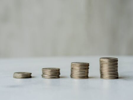 Ascending coin columns form an upward line with copy space. Illustrative concept of money growth, economic boom or financial gain / profit or banking and finance themes Stock Photo