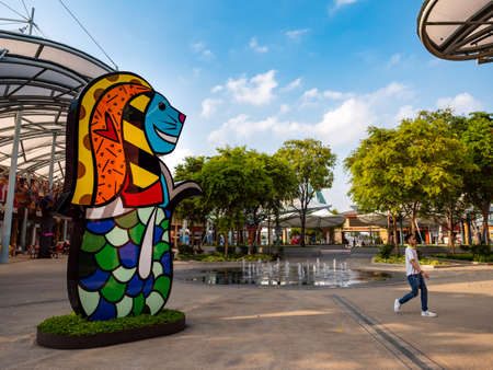 SINGAPORE – 12 MAR 2020 - An Asian man walks past a Merlion statue at the largely deserted Resort World Sentosa, Singapore. Tourist numbers have dropped due to covid-19 / coronavirus concerns