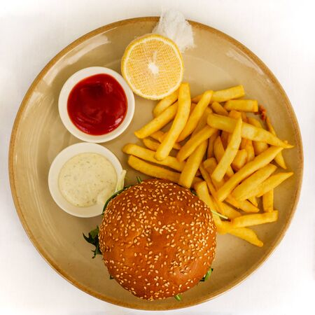 Flat lay of a burger and chips / French fries served with tomato ketchup, tartar sauce, and lemon on the side on white background