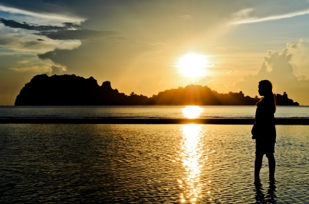 Young woman standing on the beach watching the sunrise