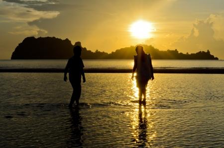 Gar�ons et filles jouent sur la plage au lever du soleil Banque d'images - 13630749