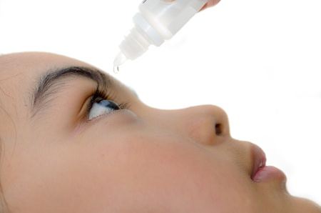 Teenage girl applying drops in her eye photo