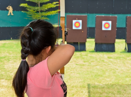 Girl aiming with a bow and arrow photo