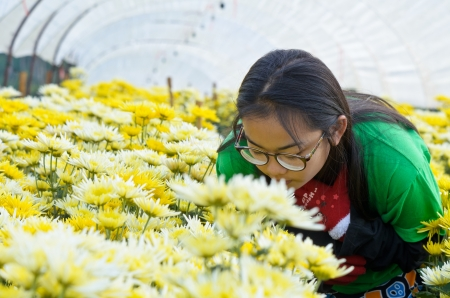Young woman enjoying smell of flowers in the morning  Thailand photo