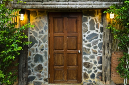 Front wooden door of residence, surrounded by nature in evening photo