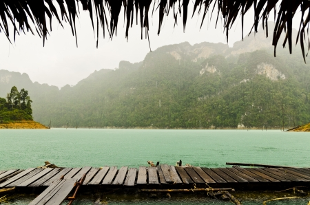 Mountain and river front of the hut while it was raining in Ratchaprapha Dam at Khao Sok National Park, Surat Thani Province, Thailand photo