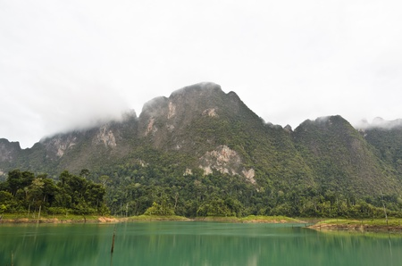 High mountains and green water in morning at Ratchaprapha Dam, Khao Sok National Park, Surat Thani Province, Thailand Stock Photo - 21559797