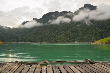 Beautiful high mountains and green water in morning, Front view of the cottage at Ratchaprapha Dam, Khao Sok National Park, Surat Thani Province, Thailand photo