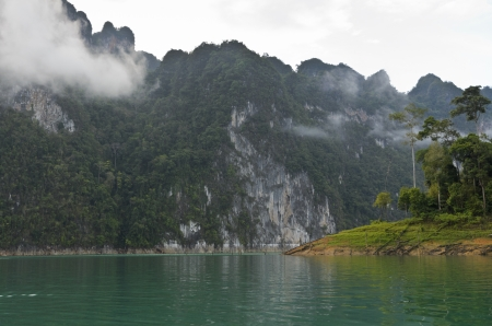 High mountains and green water in morning at Ratchaprapha Dam, Khao Sok National Park, Surat Thani Province, Thailand photo
