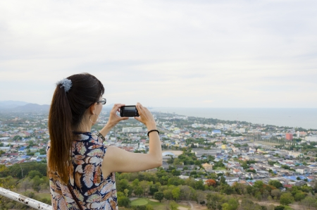 Woman using phone taking pictures of the Hua Hin city from on high  Thailand photo