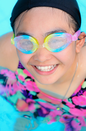 Young girl smiling and having fun swimming in a pool with blue water photo